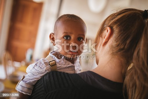 Loving young mother holding with affection adopted African American child at home