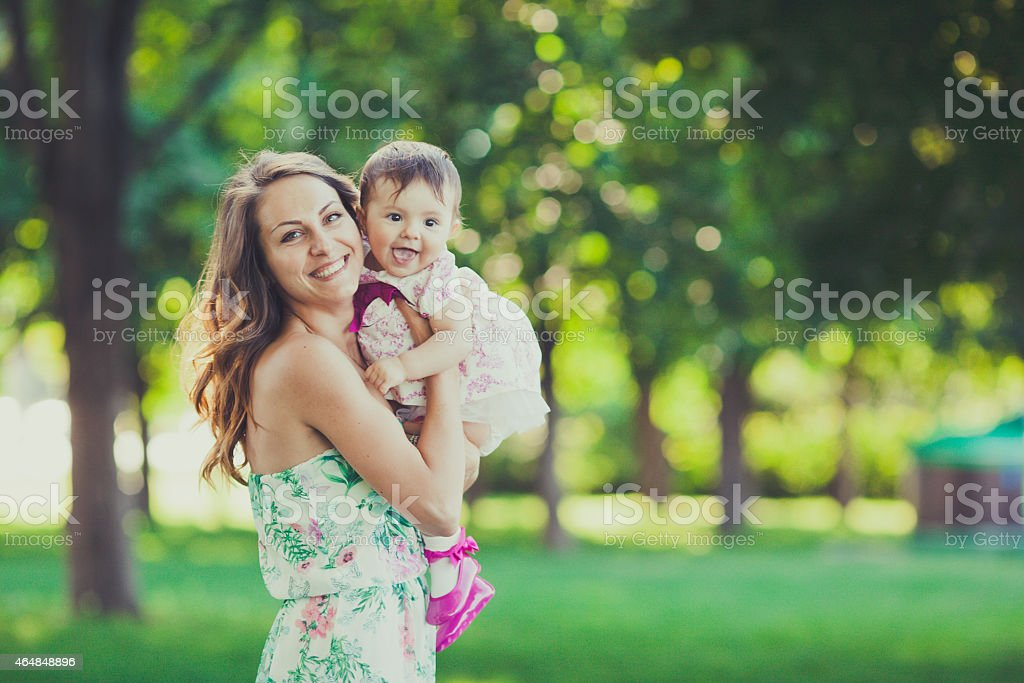 Young mother holding daughter in a park stock photo