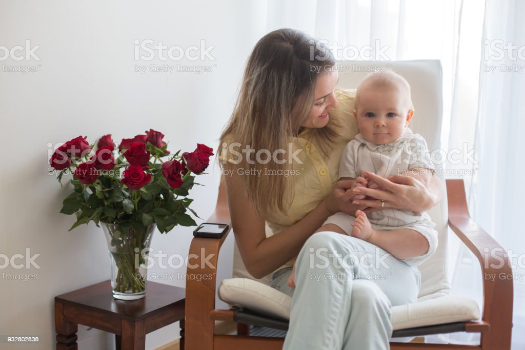 Young mother holding her baby boy, playing with him, sitting in armchair stock photo