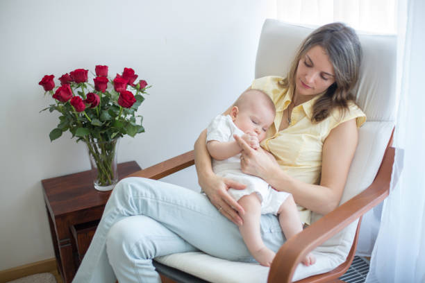 Young mother holding her baby, rocking him to sleep, sitting in armchair stock photo