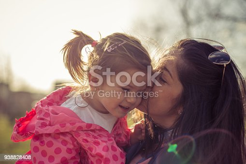 516318379 istock photo Young mother holding her daughter in the public park 938828408