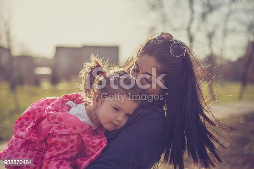 516318379 istock photo Young mother holding her daughter in the public park 938870464