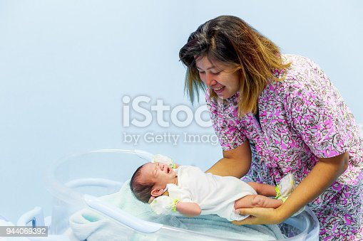 Young mother holding her newborn Asian baby crying in her arms