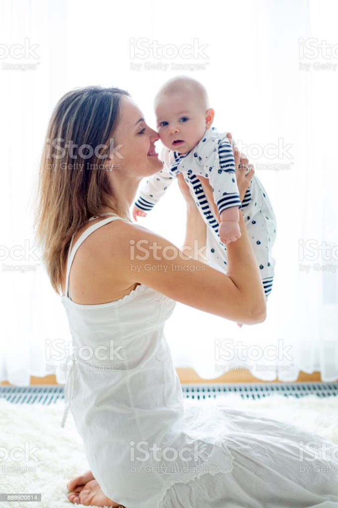 Young mother, holding her newborn baby boy at home in living room stock photo