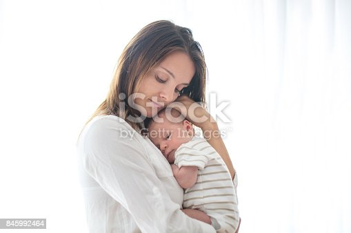 istock Young mother, holding her newborn baby boy 845992464