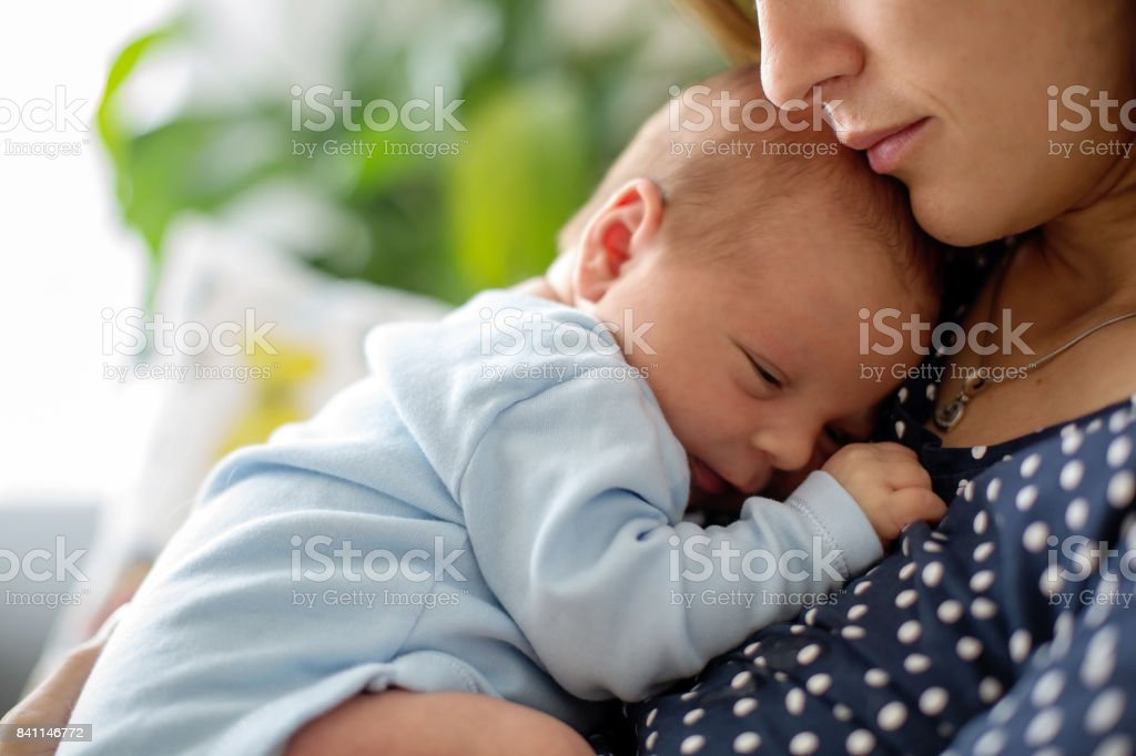 Young mother, holding tenderly her newborn baby boy stock photo