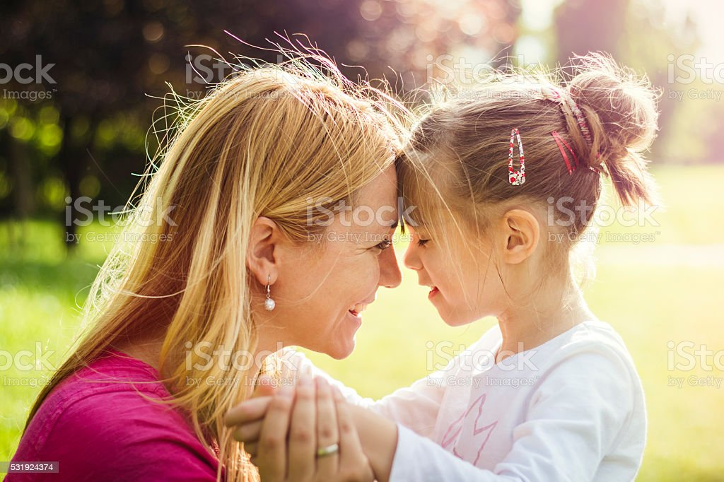 Young mother hugging her daughter in nature stock photo