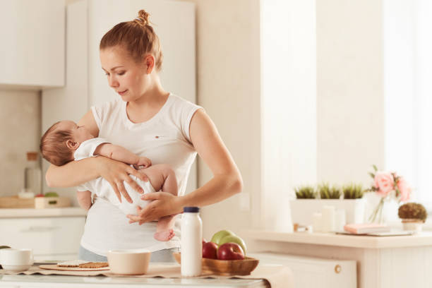 Young mother in white T-shirt rocking her baby in kitchen standing next to table covered with food stock photo