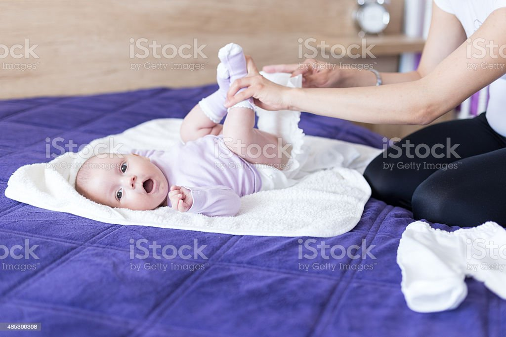 Young mother is changing diapers to her baby girl stock photo