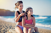 Young mother is fixing her daughter`s hair on the beach