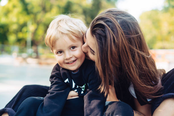 Young mother is playing with her child outside stock photo