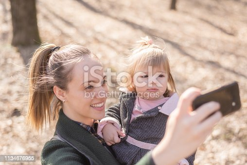 Young mother is taking a selfie with her daughter while holding her in the park on a warm sunny day