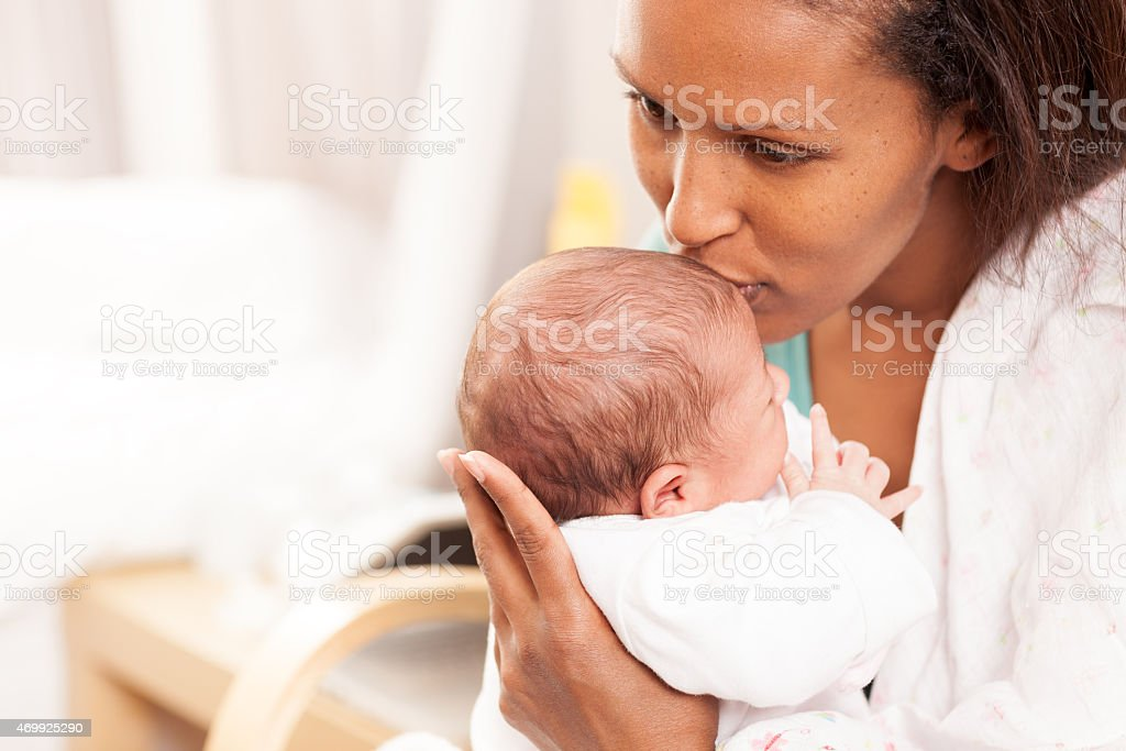 Young mother kissing her baby on the forehead stock photo