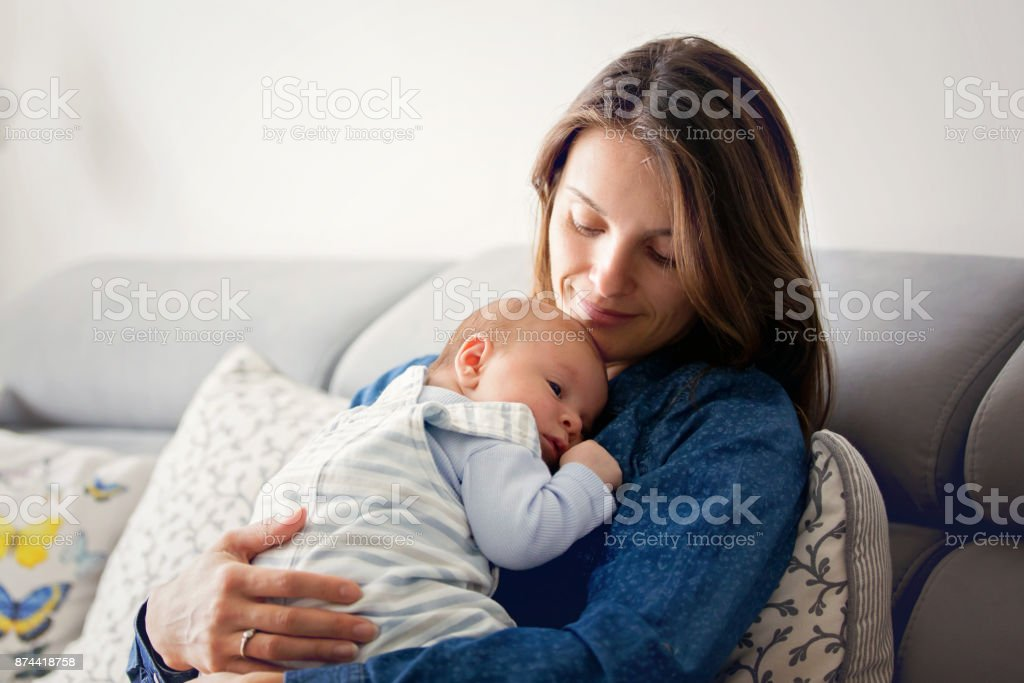 Young mother, kissing her newborn baby boy at home stock photo