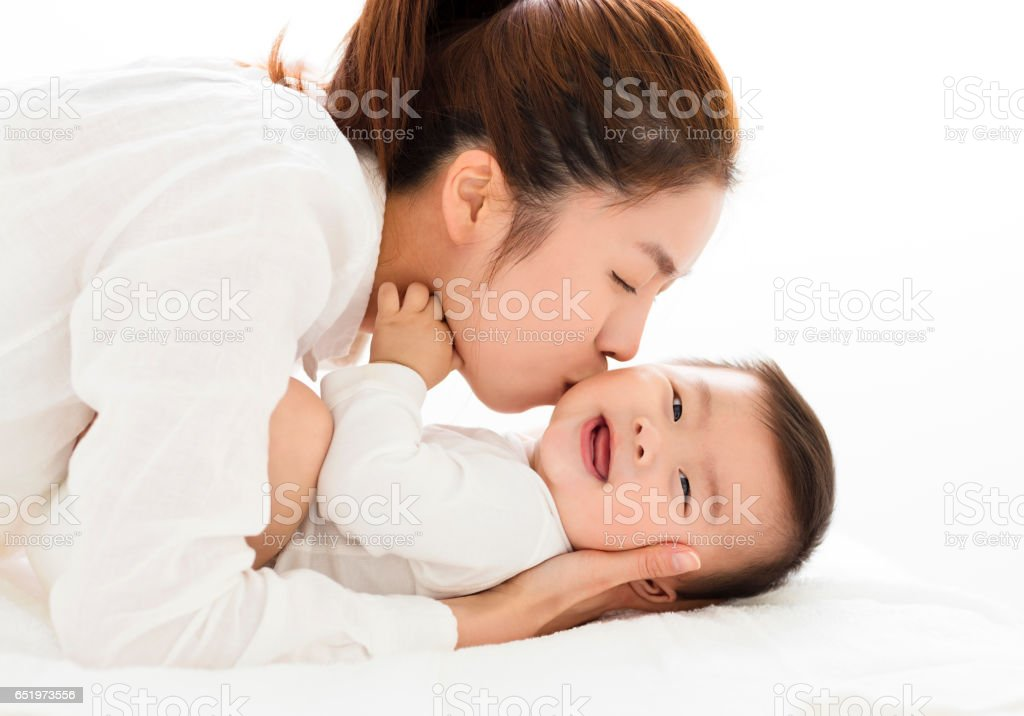 young Mother kissing sweet baby boy stock photo