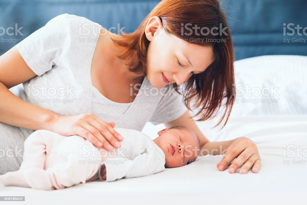 Young mother looking on her newborn baby. stock photo