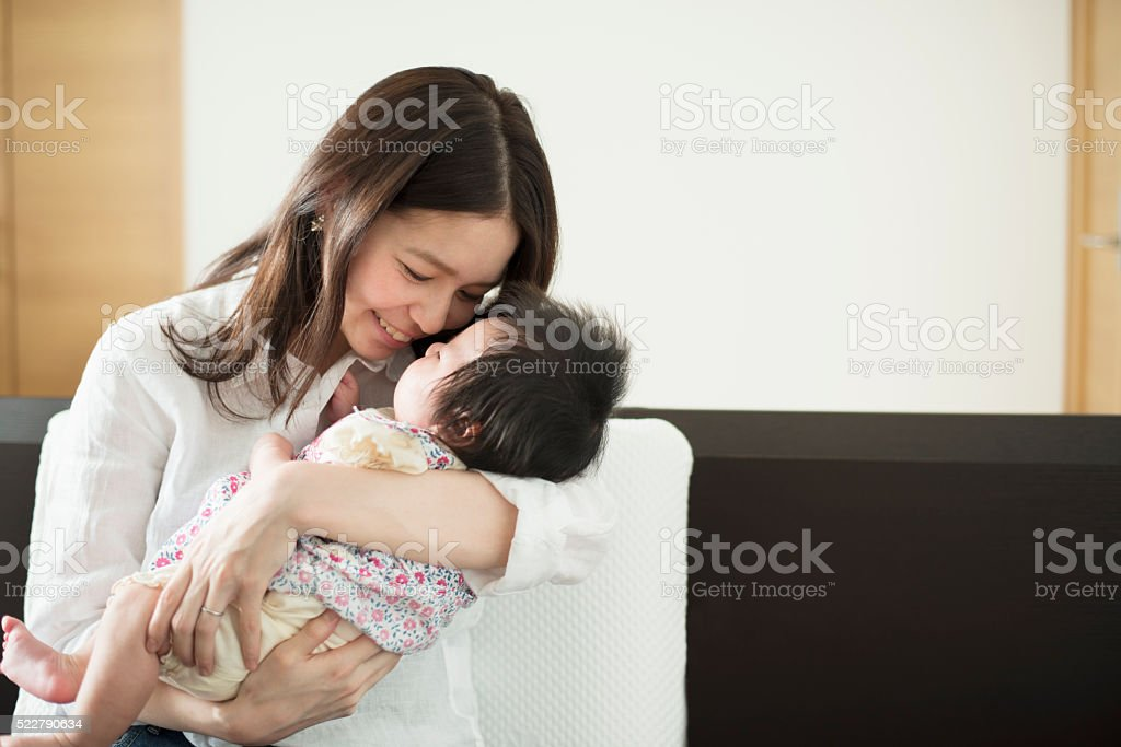 Young mother loving her baby girl at home stock photo
