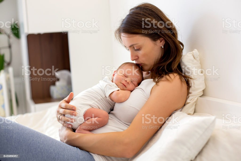 Young mother lying in bed with her newborn baby boy stock photo