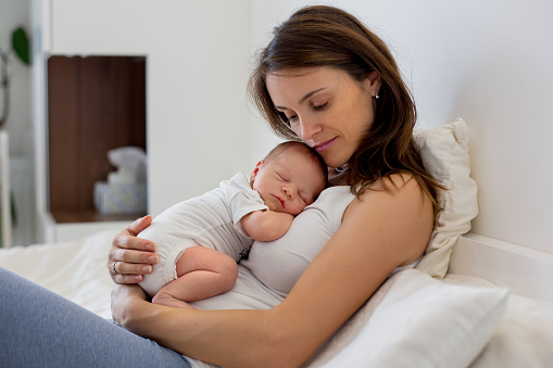 istock Young mother lying in bed with her newborn baby boy 850109704
