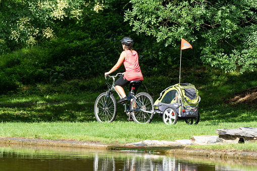 Young mom on a bike pulling child in cart on path near pond in Wyomissing, Pennslvania on August 3, 2018.