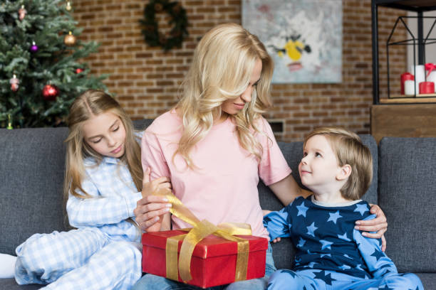 Young Mother Opening Christmas Present While Sitting With Cute Little  Children In Pajamas Stock Photo   More Pictures of Adult  e19a515ea