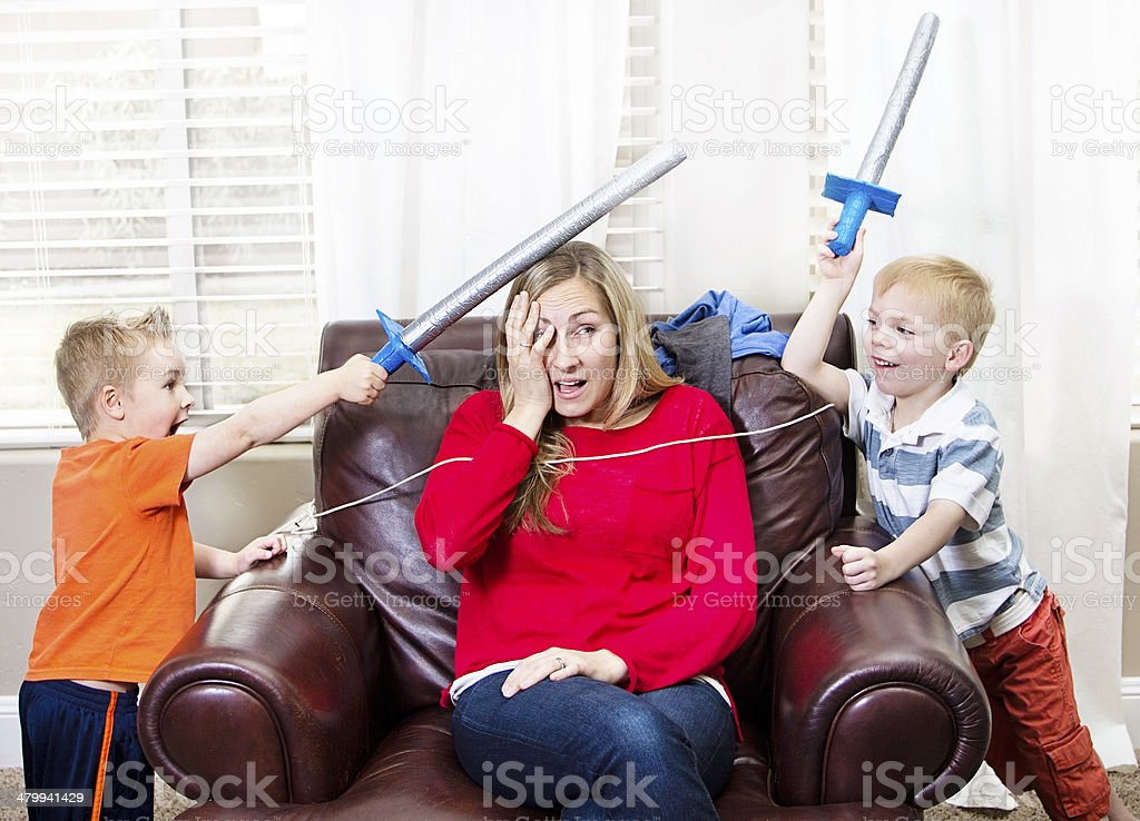 Young Mother overwhelmed by her kids stock photo