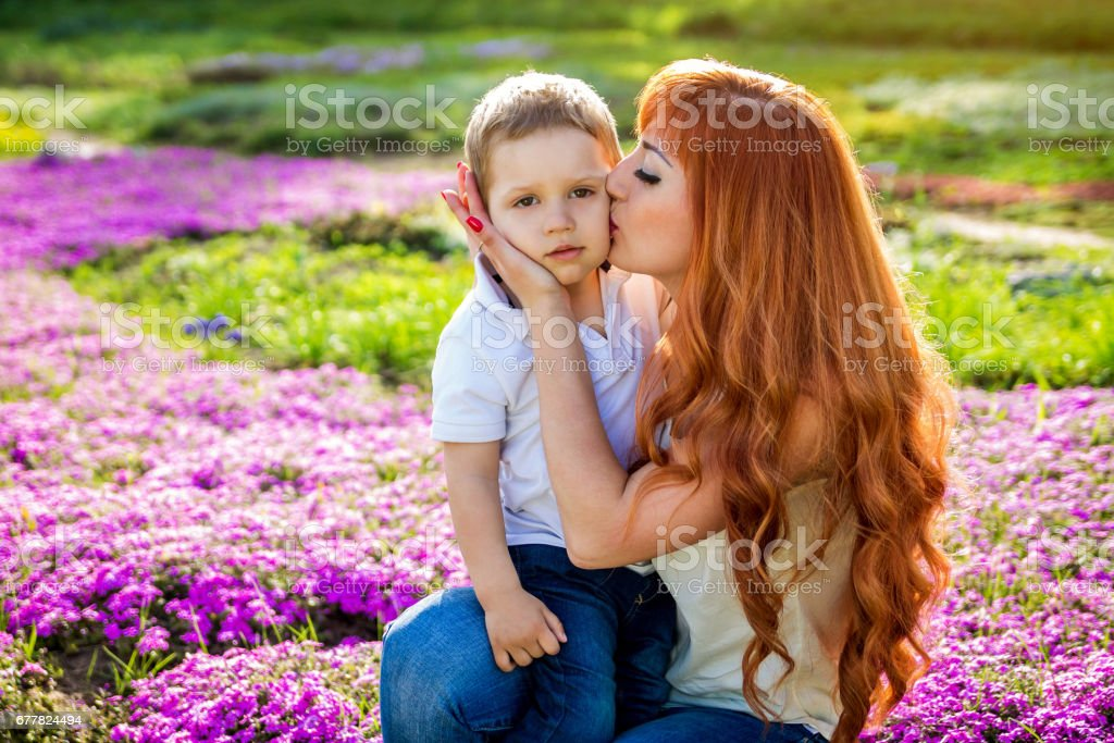 Young mother playing with her little son in the garden. Mother's Day concept royalty-free stock photo