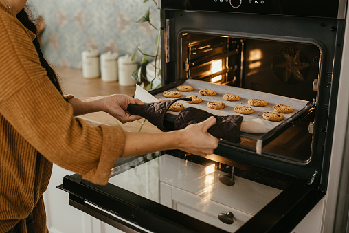 Young mother is putting a tray full of cookies which they made together with her husband and her son in the oven. Horizontal photo. Face is not visible.
