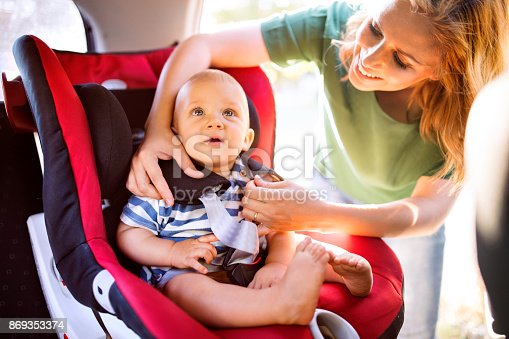 istock Young mother putting baby boy in the car seat. 869353374