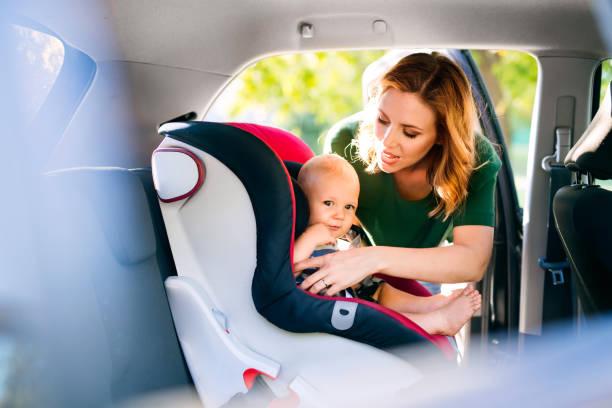 Junge Mutter putting Babyjungen in den Kindersitz. – Foto