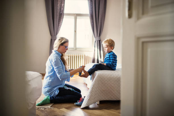 a young mother putting socks on toddler son inside in a bedroom. - take care of your jeans imagens e fotografias de stock