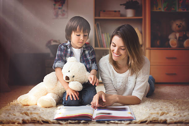 Young mother, read a book to her child, boy stock photo
