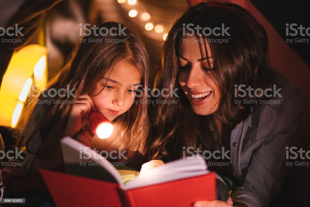 Young mother reading a book to her daughter in fort stock photo