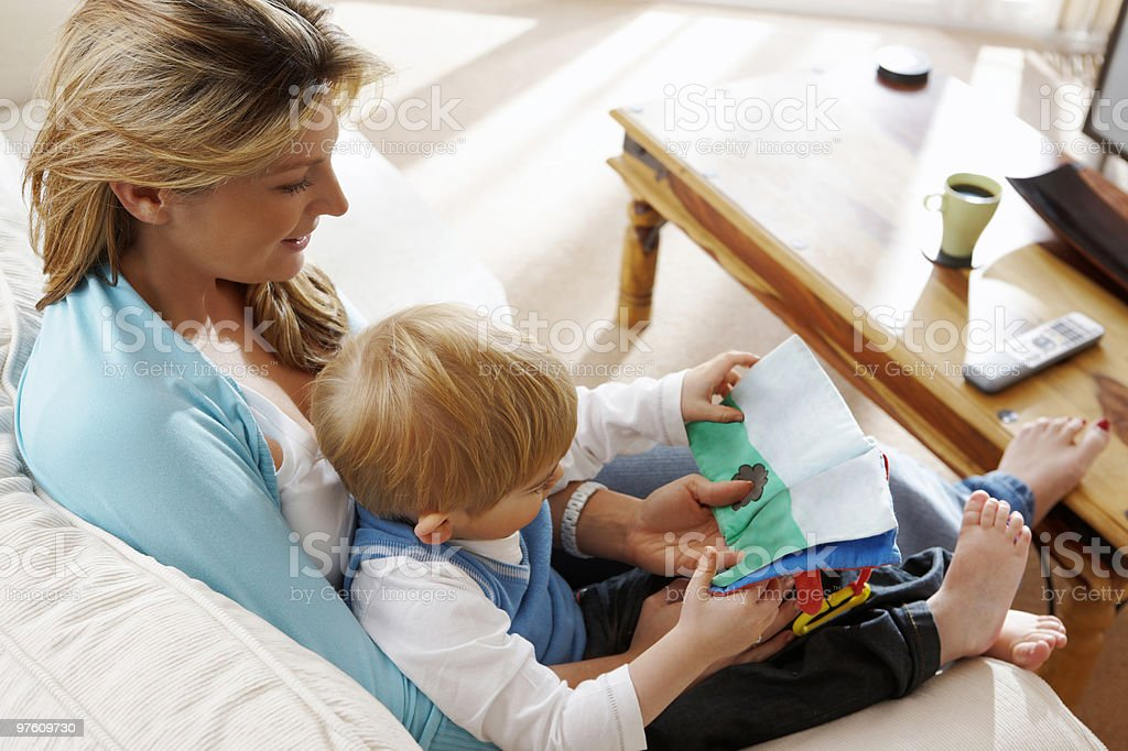 young mother reading a book to her son at home royalty-free stock photo