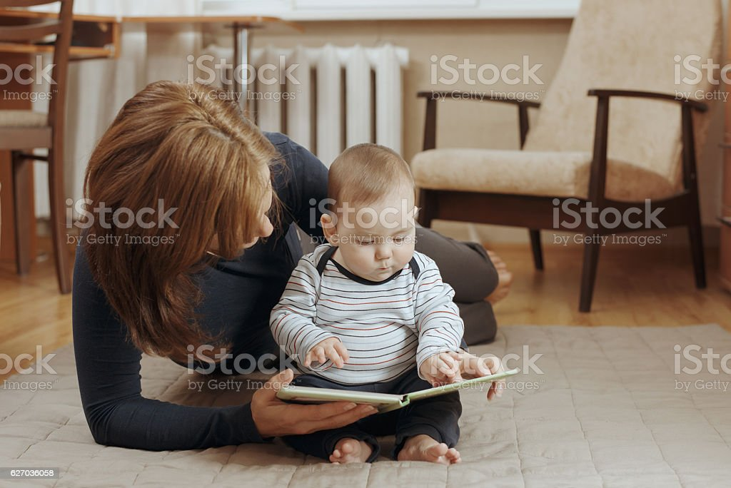 Young mother reading a story to her infant boy – Foto