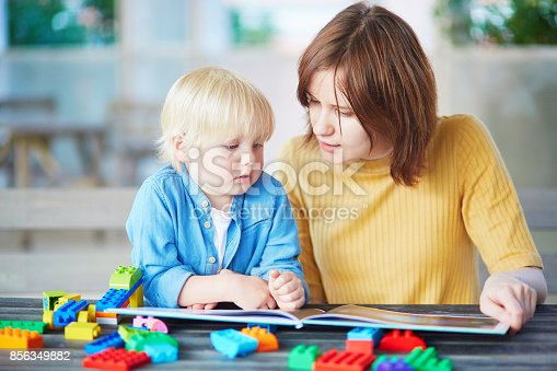 istock Young mother reading book to her son 856349882