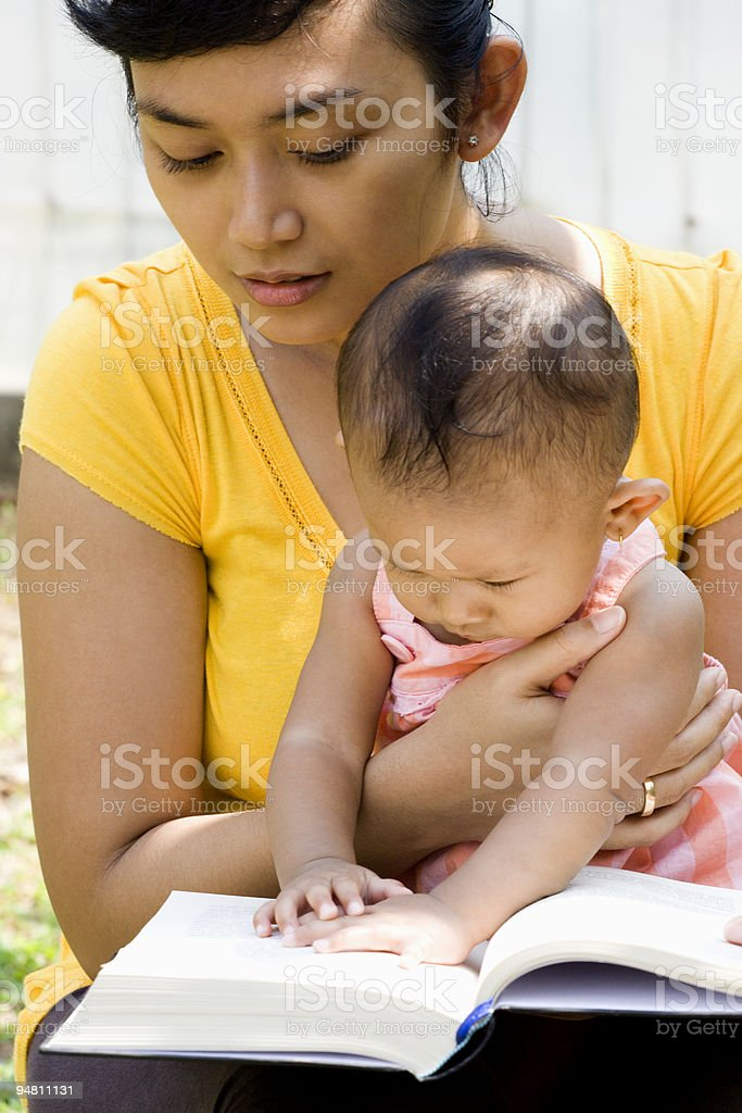young mother reading while babysitting royalty-free stock photo