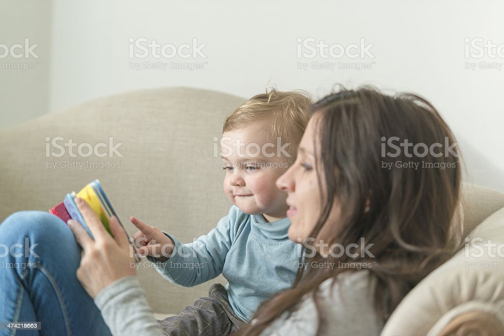 young mother reading with child stock photo