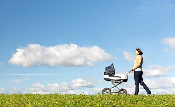 Young mother running while pushing a stroller on meadow stock photo
