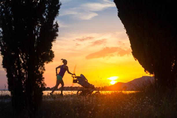 junge mutter mit kinderwagen mutterschaft bei sonnenuntergang landschaft genießen - joggerin stock-fotos und bilder