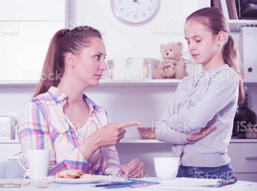 Young mother scolding her daughter stock photo