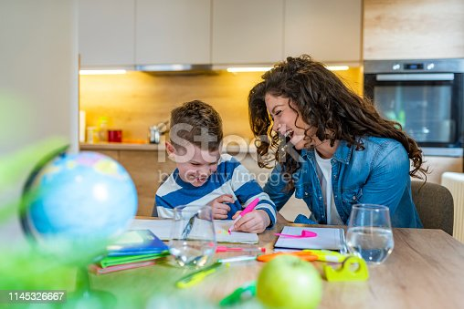 1020504438istockphoto Young mother sitting at a table at home helping her small son with his homework 1145326667