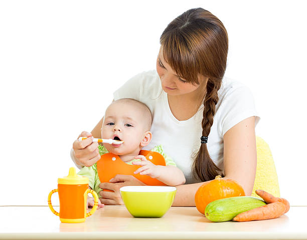 young mother spoon feeding her baby boy isolated on white stock photo