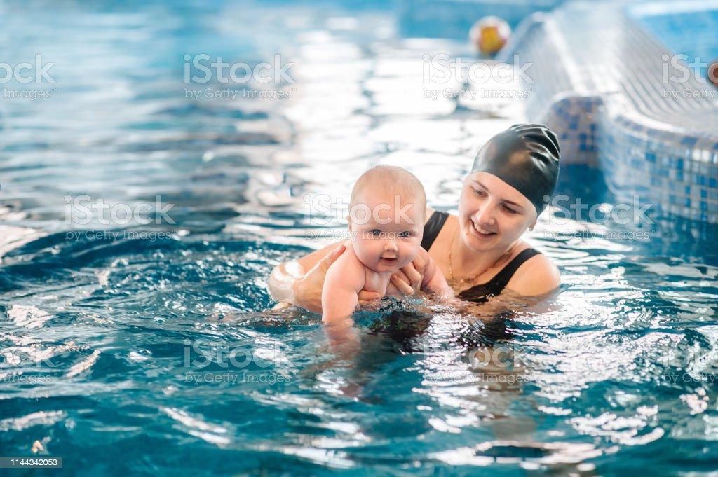 若い母親水泳インストラクターとパドルプールで幸せな少女子供に泳ぎを ...