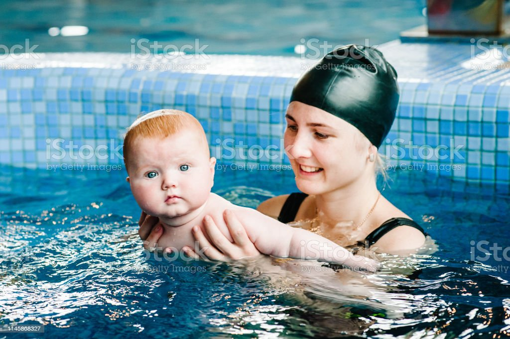 Young Mother Swimming Instructor And Happy Little Girl In ...