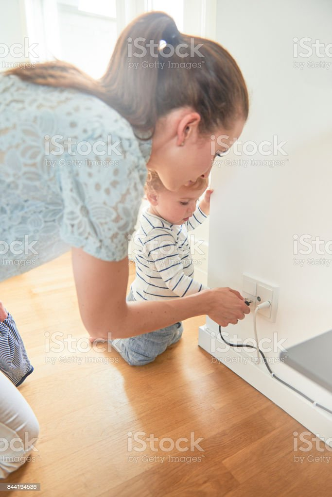 Young mother taking care of curious child stock photo