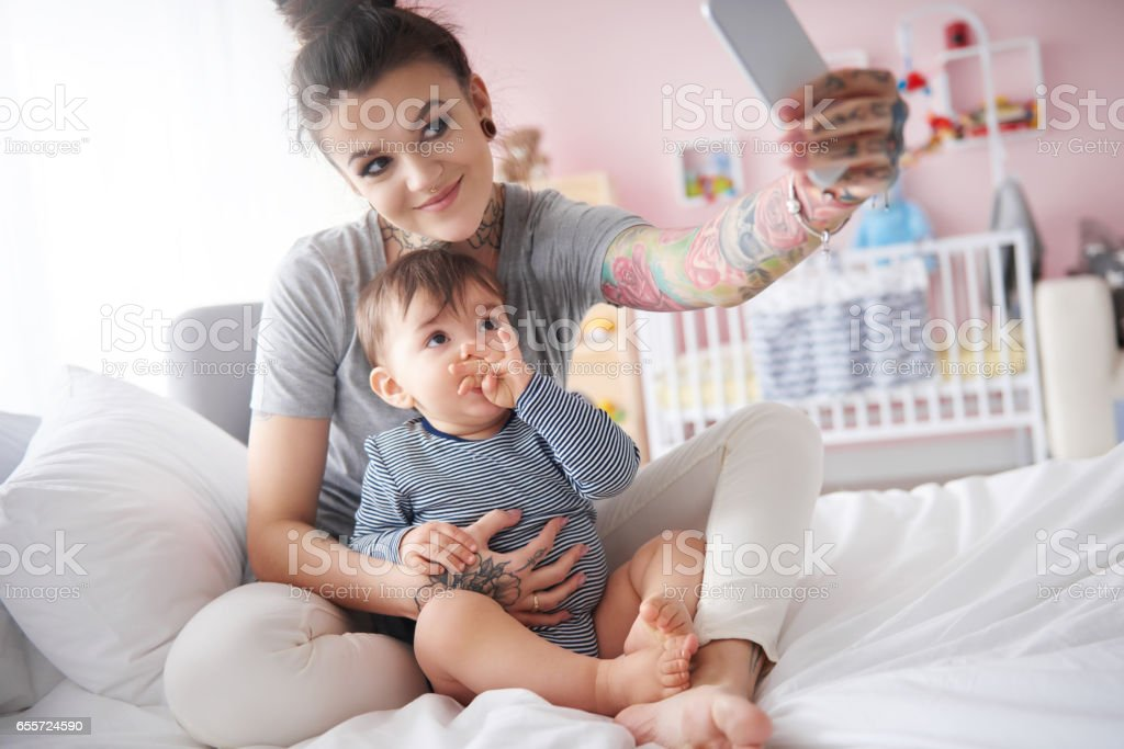 Young mother taking self portrait with smartphone stock photo
