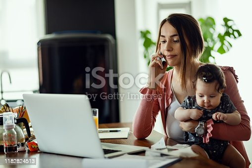 Working mother with baby daughter communicating on mobile phone while reading an e-mail on the computer.