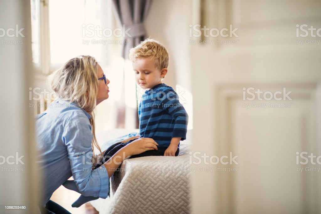 A young mother talking to her toddler son inside in a bedroom. - Royalty-free Adult Stock Photo