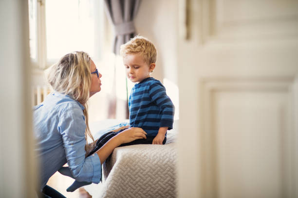 en ung mor talar till hennes barn son inne i ett sovrum. - förälder bildbanksfoton och bilder